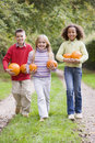 Three young friends walking on path with pumpkins Stock Image