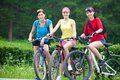 Three young girls on bicycle pretty women race in green park Royalty Free Stock Photo