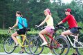 Three young girls on bicycle pretty women race in green park Royalty Free Stock Image