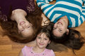 Three young girls diverse lying on a wood floor looking up at the camera one african american with red hair one hispanic and one Royalty Free Stock Photo