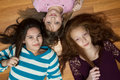 Three young girls diverse lying on a wood floor looking up at the camera one african american with red hair one hispanic and one Royalty Free Stock Photography