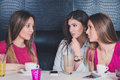 Three young girls having serious conversation in a cafe Royalty Free Stock Photography