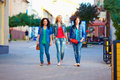 Three young girls walking the city street colorful Stock Photos