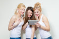Three young happy women looking at tablet pc and laughing two blond one brunette smiling girls in studio over white background Stock Photos