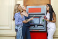 Three Young happy women in using an automated teller machine Royalty Free Stock Photo