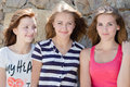 Three young happy young women girl friends have fun in city outdoors smiling looking at camera teen at stone wall Royalty Free Stock Image