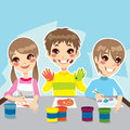 Three young kids having fun painting colorful drawings Royalty Free Stock Images