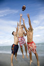Three young men playing with a ball on a beach Royalty Free Stock Photo