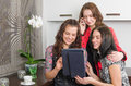 Three young women friends chatting at home and using laptop to look new photo or browsing internet for information Royalty Free Stock Photo