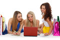 Three young women with laptop shopping beautiful cheerful girlfriends and money lie on a white background Royalty Free Stock Photography