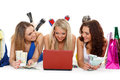Three young women with laptop shopping beautiful cheerful girlfriends and money lie on a white background Stock Photo