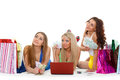 Three young women with laptop shopping beautiful cheerful girlfriends and money lie on a white background Royalty Free Stock Images