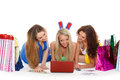 Three young women with laptop shopping beautiful cheerful girlfriends and money lie on a white background Royalty Free Stock Image