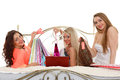 Three young women with purchases shopping beautiful cheerful girlfriends bags sit on the bed on a white background sale Stock Images