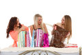 Three young women with purchases shopping beautiful cheerful girlfriends bags sit on the bed on a white background sale Royalty Free Stock Photo