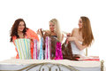 Three young women with purchases shopping beautiful cheerful girlfriends bags sit on the bed on a white background sale Royalty Free Stock Image