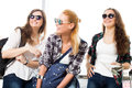 Three young women in sunglasses standing in the airport and laugh. A trip with friends Royalty Free Stock Photo