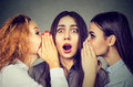 Three young women telling whispering a secret gossip each other in the ear Royalty Free Stock Photo