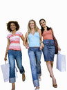 Three young women walking hand in hand with shopping bags, smiling, low angle view, cut out Royalty Free Stock Photo