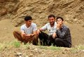 Three youngs kurdish young men sitting and smoking outside home Stock Photos