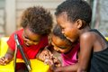 Threesome african kids having fun with tablet close up portrait of three young girls playing together on digital Stock Image