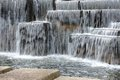 thresholds of artificial waterfall from stone blocks. concrete walking path Royalty Free Stock Photo