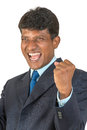 Thrilled asian man a indian south business executive in a suit cheering a win or victory with a big shout and clenched fist Stock Image