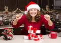 Thrilled woman during christmas excited wearing hat in the kitchen surrounded by presents Stock Images