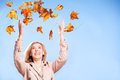 Throwing autumn leaves an attractive blonde woman throws sunlit into the air with joy Stock Photo