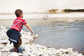 Throwing rock in water young boy Royalty Free Stock Photos
