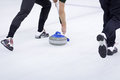 Thrown curling stone with players sweeping in the frame Stock Photo
