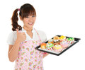 Thumb up asian female baking young bread and cupcakes wearing apron and gloves holding tray isolated on white Stock Photo