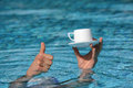 Thumb up gesture hand above water holding cup of coffee close Royalty Free Stock Photography