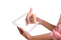 Thumb up from a screen touchscreen tablet Stock Image