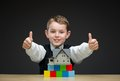 Thumbing up little boy with home model and blocks portrait of multicolored concept of construction real estate Royalty Free Stock Photos