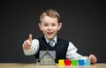 Thumbing up little boy with house model and blocks portrait of multicolored concept of construction real estate Stock Image