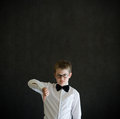 Thumbs down boy dressed up as business man sign teacher or student on blackboard background Royalty Free Stock Images