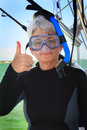 Thumbs up and all ready to snorkel a cute senior lady with white hair is suited with head mask and snorkel gear ready to dive Royalty Free Stock Photo
