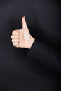 Thumbs up gesture person in dark clothing giving a of approval and success against a dark studio background with copyspace black Stock Photo