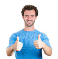 Thumbs up guy closeup portrait happy handsome young man in blue shirt showing sign gesture isolated white background positive Stock Images