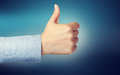 Thumbs up person giving the over blue background Stock Photos