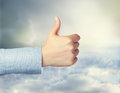 Thumbs up person giving the over cloudscape Royalty Free Stock Photo