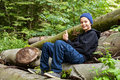 Thumbs up a teenage boy sitting on some large tree trunks and giving Stock Image