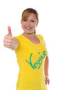 Thumbs up for veggie young attractive woman with inscription on a yellow t shirt puts her thumb Royalty Free Stock Photo