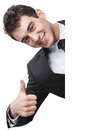 Thumbup happy businessman behind a blank sign giving a Stock Photo