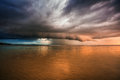 Thunder storm in the tropical sea with roll cloud approaching beach after sunset Stock Photos