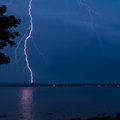 Thunderstorm over a river at night striking light thunderbolt Royalty Free Stock Photo