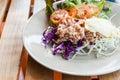 Thunfisch mit geschnittenem kohlsalat auf teller auf hölzerner tabelle Stockfotos