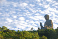 Tian tan buddha with beautiful clouds surrounded by trees and leaves Stock Photo