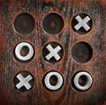 Tic tac toe game of or noughts and crosses on a wooden board with metal pieces for success or winning concept Stock Photography